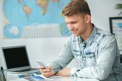 Young male travel agent consultant in tour agency using smartphone. Young man travel agent in tour agency sitting browsing smartphone internet smiling Royalty Free Stock Image