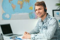 Young male travel agent consultant in tour agency wearing headset. Young man travel agent in tour agency sitting wearing headset writing looking camera smiling Royalty Free Stock Photos