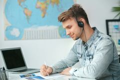 Young male travel agent consultant in tour agency writing documents. Young man travel agent in tour agency sitting wearing headset writing documents smiling Royalty Free Stock Photo
