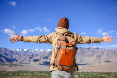 Young male travel backpacker on adventure spreading two hands in high mountain scenery Stock Images