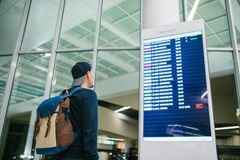 A young male traveler with a backpack in casual style looks at the information board at the airport. Getting information. About the flight Stock Images