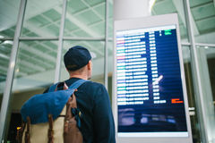 A young male traveler with a backpack in casual style looks at the information board at the airport. Getting information Stock Photos