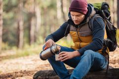 young male traveler with backpack drinking tea from thermos stock photography