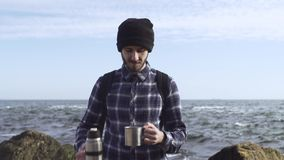 Young male traveler. With backpack relaxing on the autumn beach stock video footage
