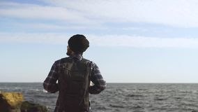 Young male traveler. With backpack relaxing on the autumn beach stock video