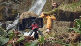Young male traveler blogger in sitting enjoys a beautiful waterfall. Hiking in the mountains. A hiker sits at a