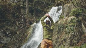 Young male traveler in enjoys a beautiful waterfall. Hiking in the mountains. The hiker runs to the waterfall, raises