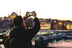 Young male traveler photographing a beautiful view of the Bosphorus in Istanbul. View from the back royalty free stock image
