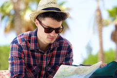 Young male traveler reading map outside. Close up portrait of a young male traveler reading map outside Stock Images