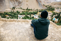Young male traveler sitting on the sand cliff, thinking about something in Leh, Ladakh, India Stock Photo