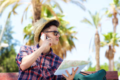 Young male traveler talking on mobile phone and holding map Royalty Free Stock Photo