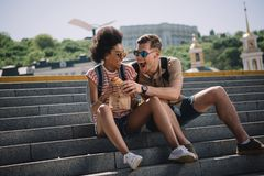 Young male traveler trying to eat girlfriend. Croissant on stairs stock images