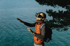 Young Male Traveler in virtual glasses on the background of the. Sea Royalty Free Stock Image
