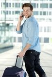 Young male traveler walking with mobile phone and bag Stock Photos