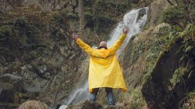 Young male traveler in a yellow raincoat enjoys a beautiful waterfall. Hiking in the mountains. The hiker runs to the