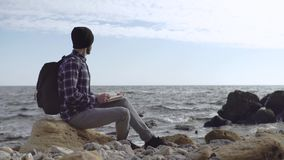 Young male traveler. With backpack relaxing on the autumn beach stock footage