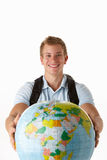 Young male traveller with globe. Young male traveller holding out globe isolated on white background Royalty Free Stock Photo