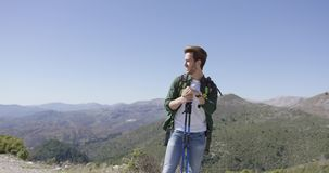 Young male with trekking poles looking away stock footage