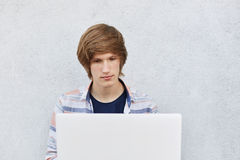 Young male with trendy haircut sitting in front of opened laptop reading electronic book with serious expression being focused on Stock Photo