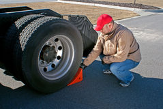Young male truck driver chocking wheels for safety. Young male truck driver wearing red cap is shown placing a chock behind the outside rear tractor tire Stock Photography