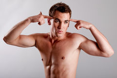Young male underwear model. Young man with hands on his head making gun gesture Stock Photography