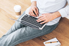 Young male using laptop floor. Young male sitting on wooden floor with coffee cup and notepad, using laptop Stock Image
