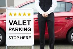 Young Male Valet Standing Near Valet Parking Sign. Close-up Of Male Valet Standing Near Valet Parking Sign royalty free stock photos