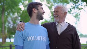 Young male volunteer and mature gentleman smiling to each other, social support