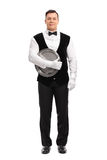 Young male waiter holding a tray. Full length portrait of a young male waiter holding a tray and looking at the camera isolated on white background Royalty Free Stock Images