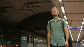 Young male walking along half-empty platform in subway, urban public transport. Stock footage stock video