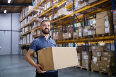 Male warehouse worker with a large box. Young male warehouse worker or a supervisor holding a large box Stock Photography