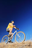 A young male wearing yellow shirt and helmet on a bike Royalty Free Stock Photos