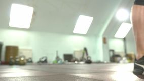 Young Male Weightlifter In Sneakers Training With Barbell. Close-up - Young Male Weightlifter In Sneakers Training With Barbell During Workout At The Gym. The stock footage