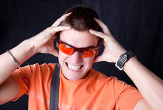 Young  male whit orange sunglasses hold a head, Royalty Free Stock Image