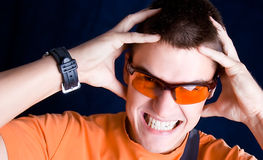 Young  male whit orange sunglasses hold a head, Stock Images