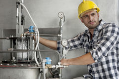 Young male worker examining machine in industry Royalty Free Stock Photos