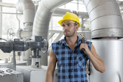 Young male worker holding wrench in industry Stock Image