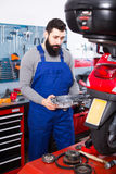 Young male worker looking at motorcycle detai. L to fix it in workshop Stock Photos
