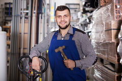 Young male worker showing his working tools. At workshop Royalty Free Stock Photos