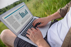 Young male worker using laptop in nature. Close up of male hands typing on computer. Man is sitting in meadow Stock Photos