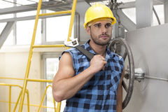 Young male worker with wrench leaning on large industrial valve Royalty Free Stock Photos