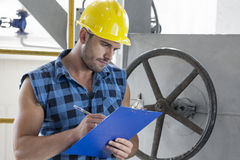 Young male worker writing on clipboard by large valve in industry Stock Images