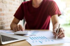 Young male working analysis finance with calculate about cost on. Investment, planning data on document, business strategy and accounting concept Royalty Free Stock Images