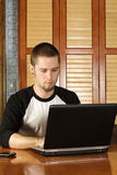 Young male working on laptop. From home Royalty Free Stock Image