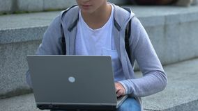 Young male working on laptop outdoors, it genius or smart teenage hacker, app