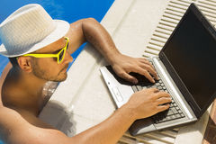 Young male working on laptop from a swimming pool. Man in the swimming pool with hand on laptop keyboard. He is wearing hat and sunglasses Royalty Free Stock Image