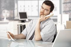 Young male working in office talking on phone Royalty Free Stock Image
