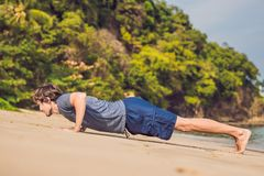 Young male working out on beach, sporty man doing exercises stock photos