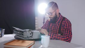 Writer`s day concept. Young male writer in a dark room typing on a typewriter. Young male writer in a dark room typing on a typewriter stock video