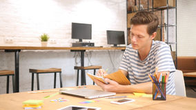 Young male writing in Notebook with Pen, Modern Loft Office stock images